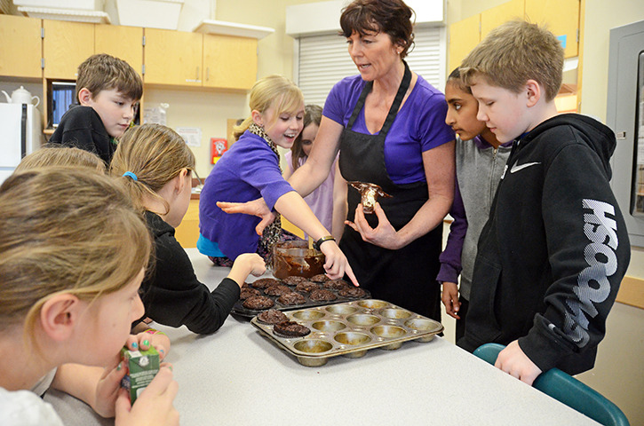 Melanie Brown Preston referees kids laying claim to cupcakes in her after school cooking class at Greendale elementary.— Image Credit: Paul J. Henderson
