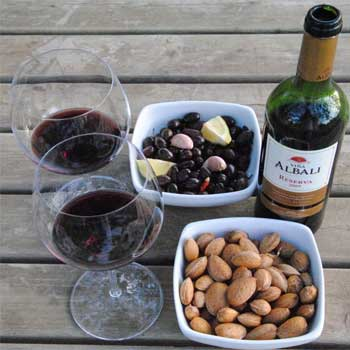 two glasses of wine next to bowls of nuts and dried fruit and the bottle of red wine